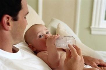 Een vader die flesvoeding geeft