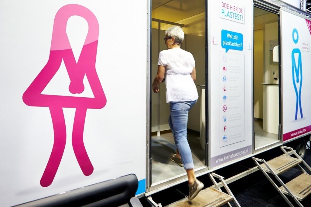 Een vrouw loopt een toilet binnen