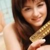 Een meisje met een strip anticonceptiepillen in haar hand